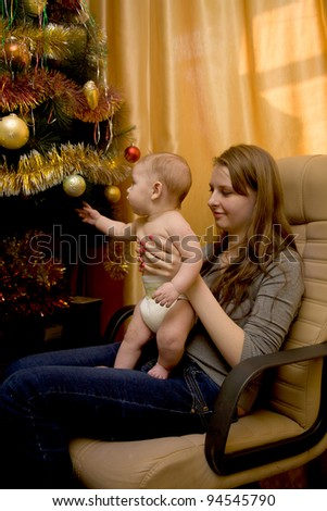 Portrait of angelic baby and his mother near the Christmas tree - stock photo
