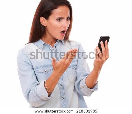 Portrait of angry adult female on blue blouse reading a message on her cell while screaming on isolated white bacckground - stock photo