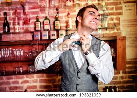 Portrait of angry and stressed bartender or barman with bowtie behind the bar with alcoholic drinks around. Stressful lifestyle of barista concept - stock photo