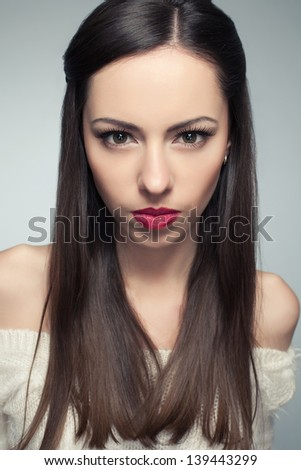 Portrait of angry beautiful long-haired brunette posing over light-gray background. Healthy skin. Studio shot