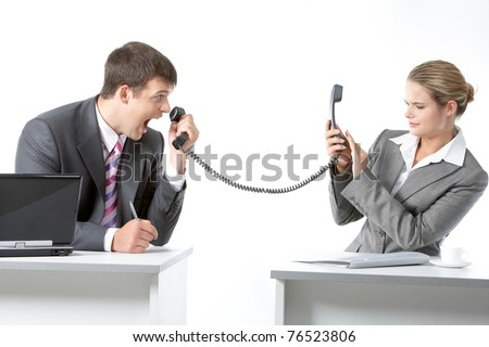 Portrait of angry boss shouting into telephone receiver at his secretary - stock photo