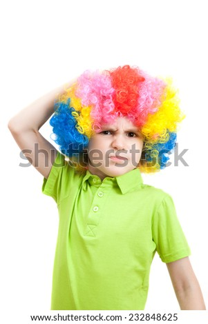 Portrait of angry  boy in a colorful wig - stock photo