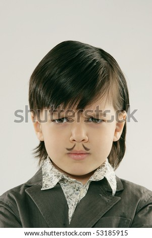 Portrait of angry  boy with moustache. Studio shot - stock photo