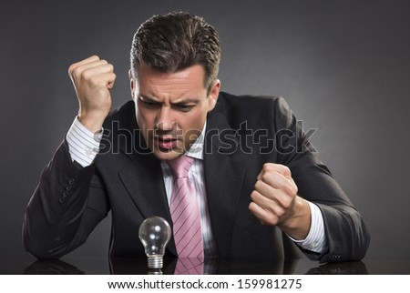 Portrait of angry businessman with clenched fists looking at light bulb, seeking desperately for smart business solution over dark background. - stock photo