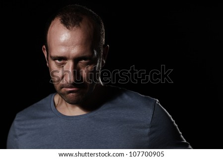 Portrait of angry man on black background looking aggressive at camera - stock photo