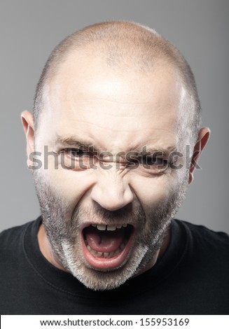 portrait of angry man screaming isolated on gray background - stock photo