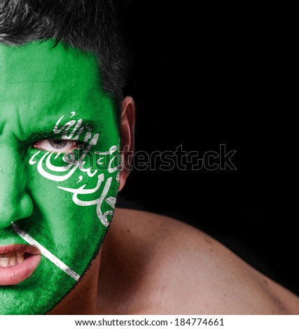 Portrait of angry man with painted flag of Saudi Arabia - stock photo