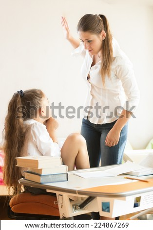 Portrait of angry mother hitting intimidated daughter