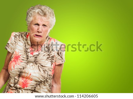 Portrait Of Angry Senior Woman Isolated On Green Background