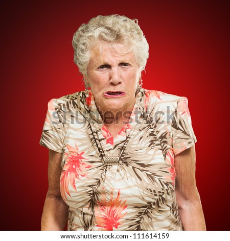 Portrait Of Angry Senior Woman Isolated Over Red Background - stock photo
