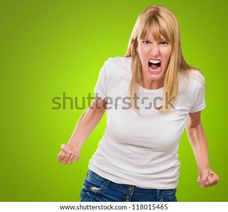 Portrait Of Angry Woman against a green background - stock photo