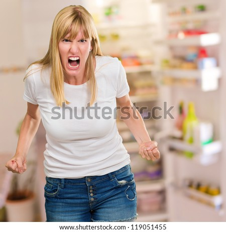 Portrait Of Angry Woman by a fridge full of food - stock photo