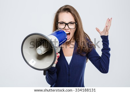 Portrait of angry woman screaming in megaphone isolated on a white background