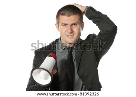 Portrait of angry young business man holding megaphone. - stock photo