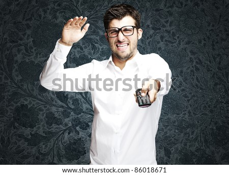portrait of angry young man changing channel with tv control against a vintage background