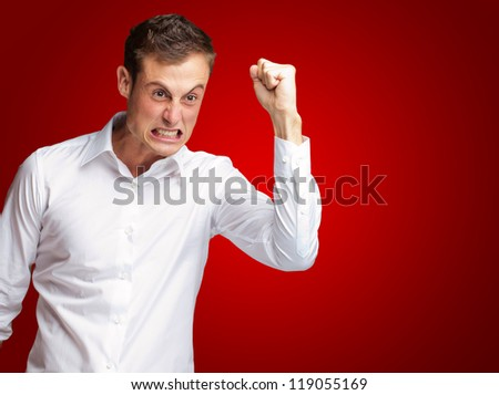Portrait Of Angry Young Man Clenching His Fist On Red Background - stock photo