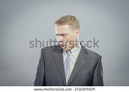 Portrait Of Angry Young Man Shouting Over Grey Background - stock photo