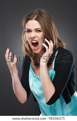 Portrait of angry young woman shouting on mobile phone on gray background isolated - stock photo