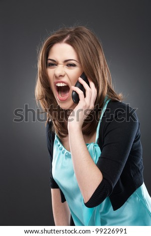 Portrait of angry young woman shouting on mobile phone on gray background isolated