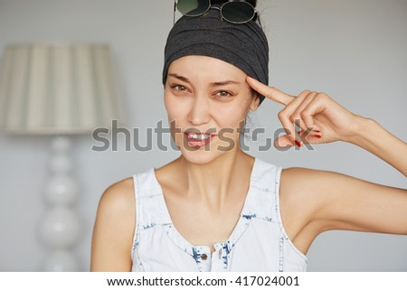 Portrait of annoyed, unhappy abd displeased woman gesturing her finger against her temple: are you crazy? asking to think carefully, isolated on home interior background. Negative face expressions - stock photo