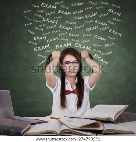 Portrait of anxious teenage girl grabs her hair ties when studying for exam - stock photo
