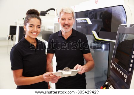 Portrait Of Apprentice Working With Engineer On CNC Machine