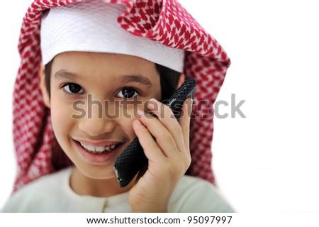 Portrait of arabian kid speaking on phone - stock photo