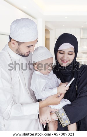 Portrait of Arabian little boy using a smartphone with his parents at home