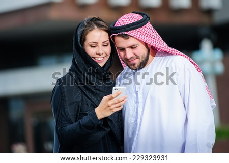 Portrait of Arabic dressed yang couple play with mobile phone.. - stock photo