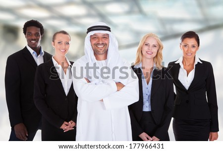 Portrait Of Arabic Man Standing With Businesspeople Around - stock photo