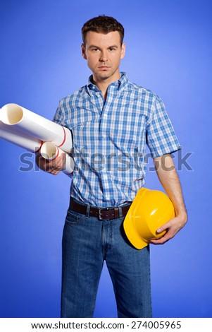 Portrait of architect holding blueprint and hardhat - stock photo