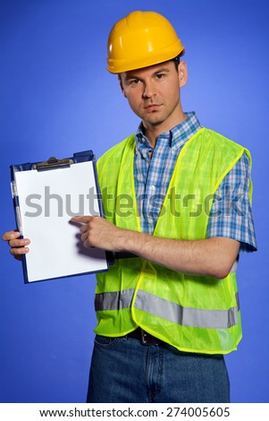 Portrait of architect in coveralls and hardhat pointing at clipboard - stock photo
