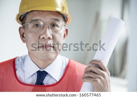 Portrait of architect in hardhat holding rolled up blueprint indoors - stock photo