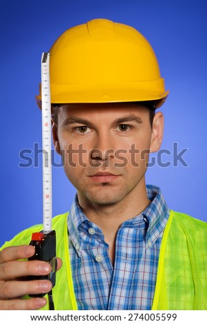 Portrait of architect in hardhat holding tape measure - stock photo