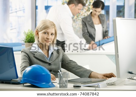 Portrait of architect sitting in office, smiling, coworkers working in background.? - stock photo