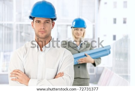 Portrait of architect standing in office in hardhat, looking at camera, coworker with work plan in background,? - stock photo