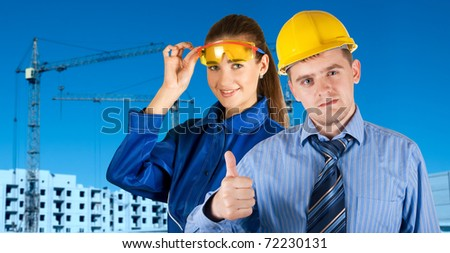 Portrait of architects at in front of construction site, building and crane. - stock photo