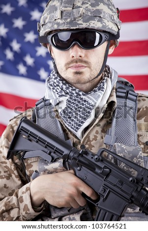 Portrait of armed american soldier in camouflage over american flag - stock photo