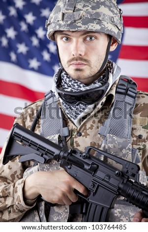Portrait of armed American soldier over american flag in background - stock photo