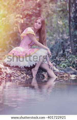 Portrait of asia beautiful girl in ballet dress on nature, flare and vintage effect