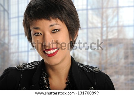 Portrait of Asian American businesswoman indoors with building in background - stock photo