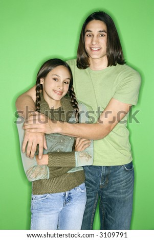Portrait of Asian-American girl and teen boy standing with arms around eachother smiling against green background. - stock photo