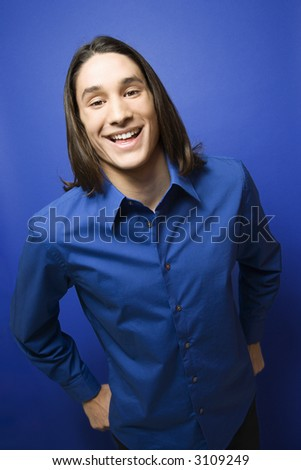 Portrait of Asian-American teen boy smiling at camera against blue background. - stock photo