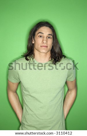 Portrait of Asian-American teen boy standing against green background.
