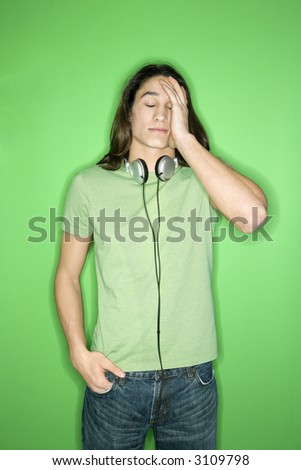 Portrait of Asian-American teen boy with headphones around neck and hand on forehead standing against green background.