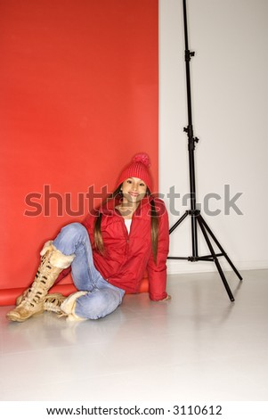 Portrait of Asian-American teen girl in studio setting sitting on floor next to light stand. - stock photo