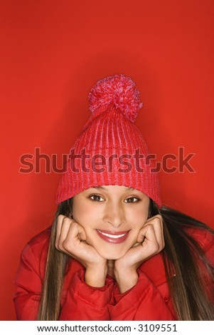 Portrait of Asian-American teen girl wearing winter hat resting head on hands against red background. - stock photo