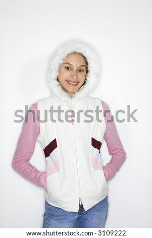 Portrait of Asian-American teen girl with hands in coat pockets and furry hood on head smiling against white background. - stock photo