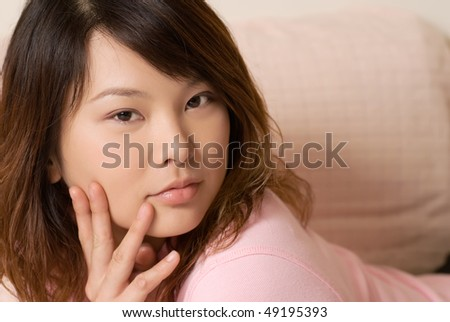 Portrait of Asian beauty in home with cool expression and eyes. - stock photo