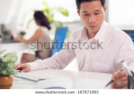 Portrait of Asian businessman planning work in office and his secretary working on background